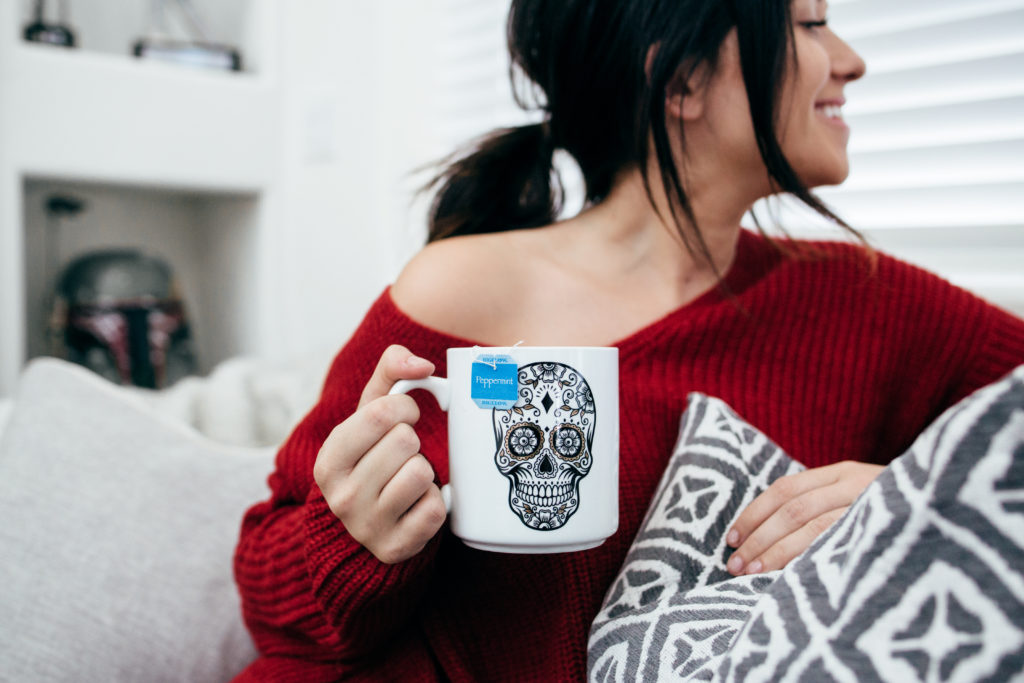 Erin Aschow Fashion Blogger Red Off the Shoulder Sweater Drinking Tea on the Couch