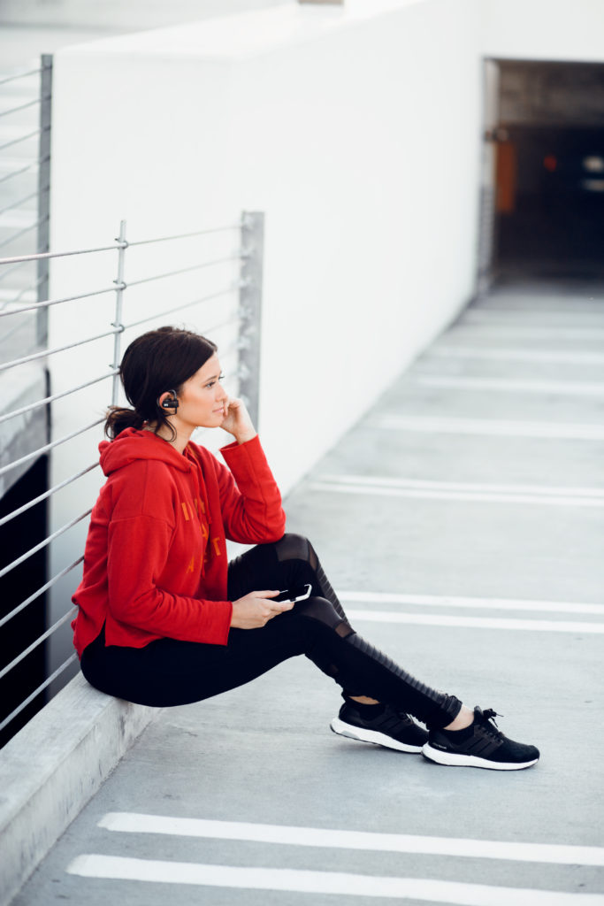 Erin Aschow fashion blogger listening to music in a red sweatshirt and moto leggings with adidas ultra boost tennis shoes