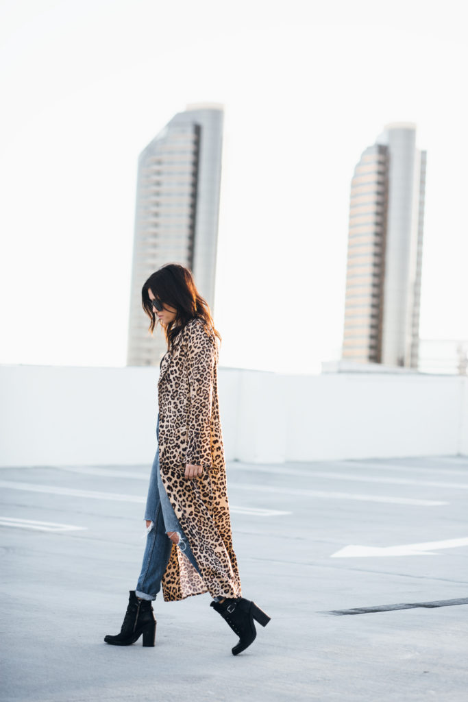 Erin Aschow San Diego Fashion Blogger - Roof Top Photoshoot - Leopard Print House of Harlow Duster from Revolve with Distressed High Waisted Jeans, Studded Sunglasses, Military Dolce Vita Boots and a black bodysuit