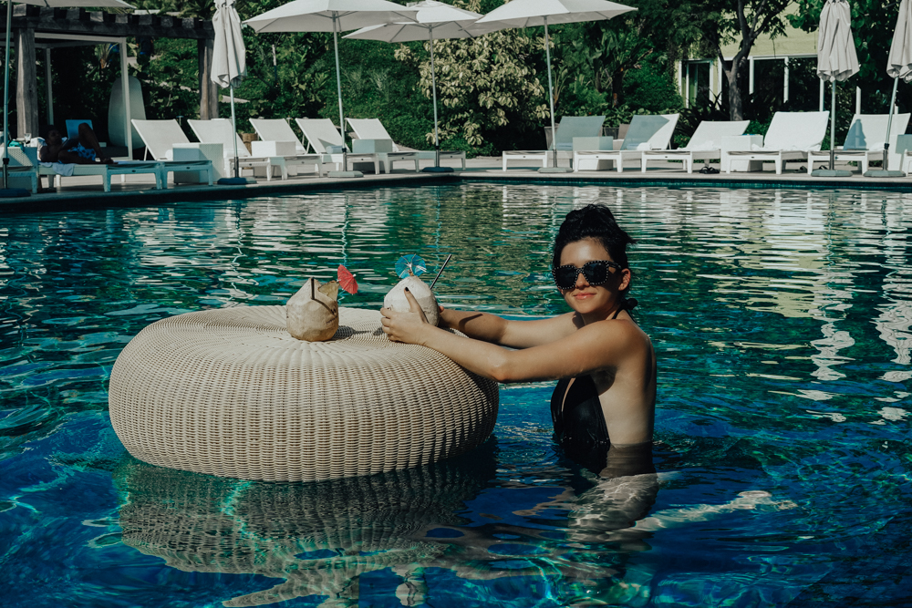 Erin Aschow blogger swimming drinking in pool coconuts