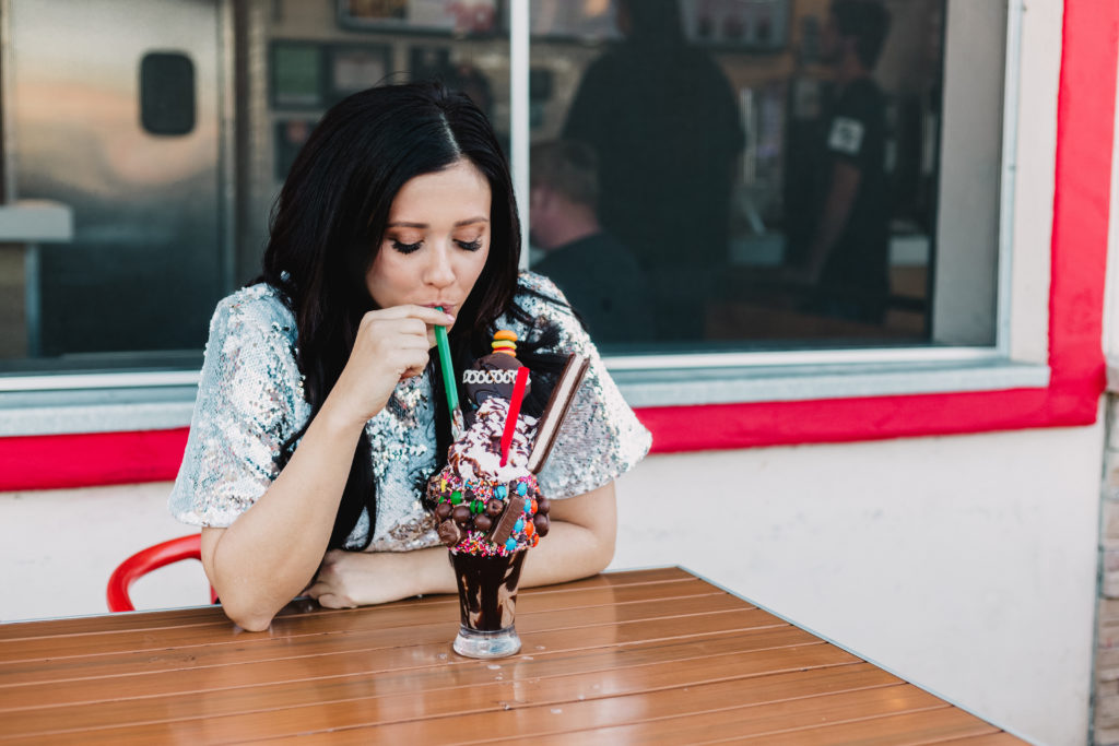 Erin Aschow Revenge Bakery Travel & Food Blogger eating an over the top milkshake from Funky Fries & Burgers