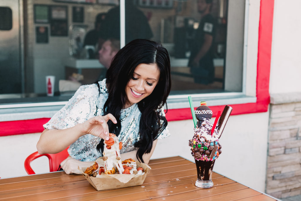 Blogger eating an Over the Top Milkshake and Pizza Fries at Funky Fries & Burgers