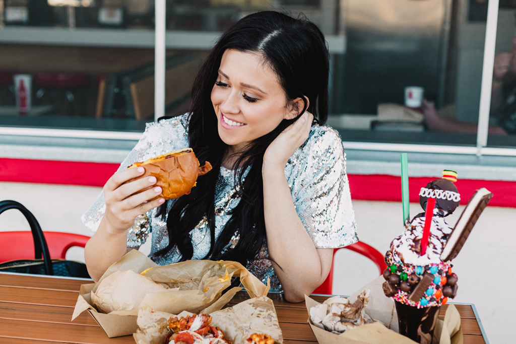 Blogger eating an Mac N Cheese Burger at Funky Fries & Burgers